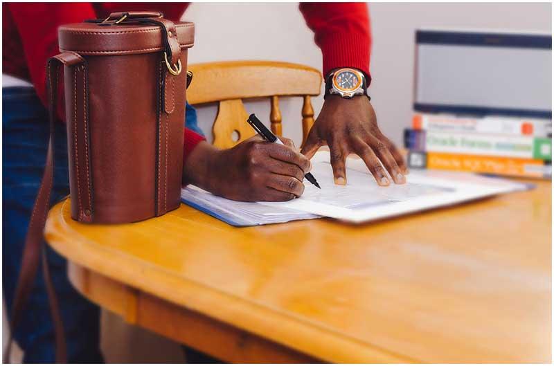 Persona firmando contrato de arrendamiento.